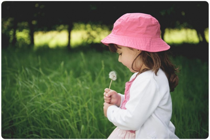 Young child blowing the seeds off a dandelion