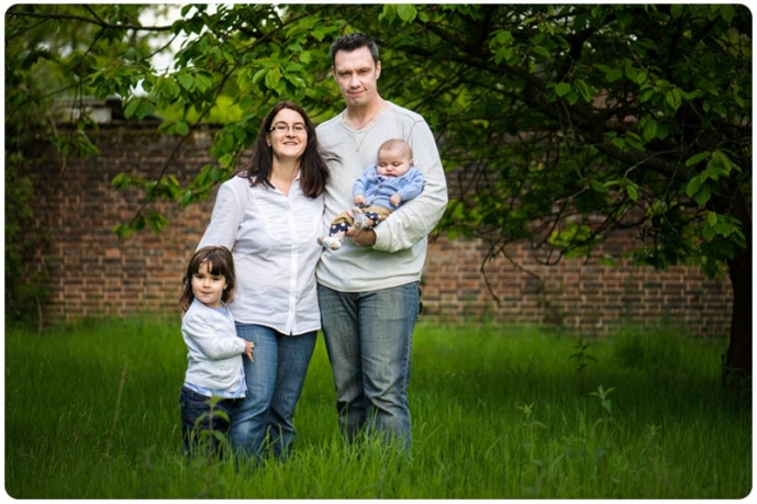 Professional group portrait of family in long grass meadow