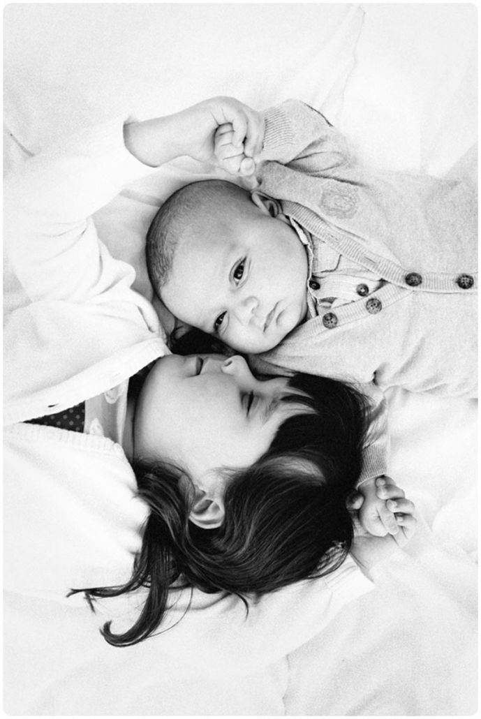 Baby Brother and older sister lay next to each other for a photography