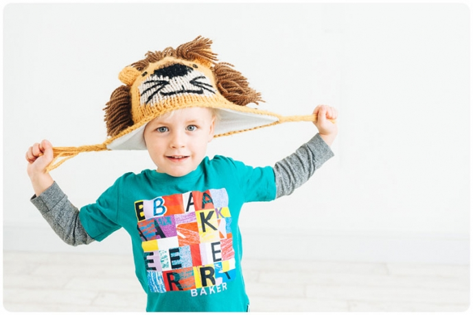 Child having fun with knitted lion hat