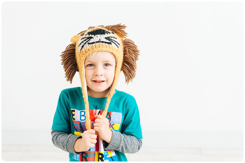 Young boy wearing a lion knitted hat