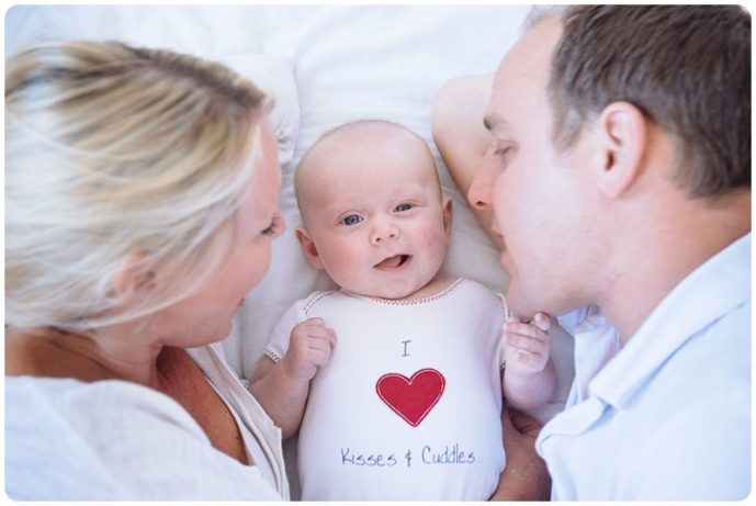 family with young baby snuggle on a bed