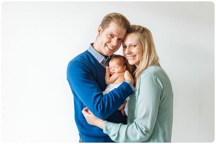 New parents cuddle their newborn baby daughter