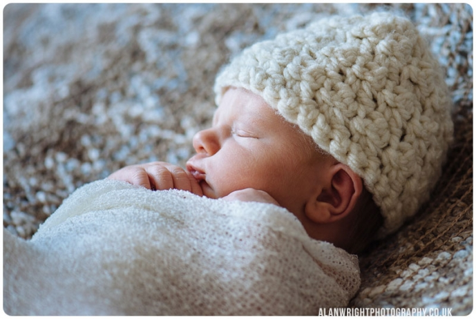Newborn Baby sleeping, wrapped up and cosy.