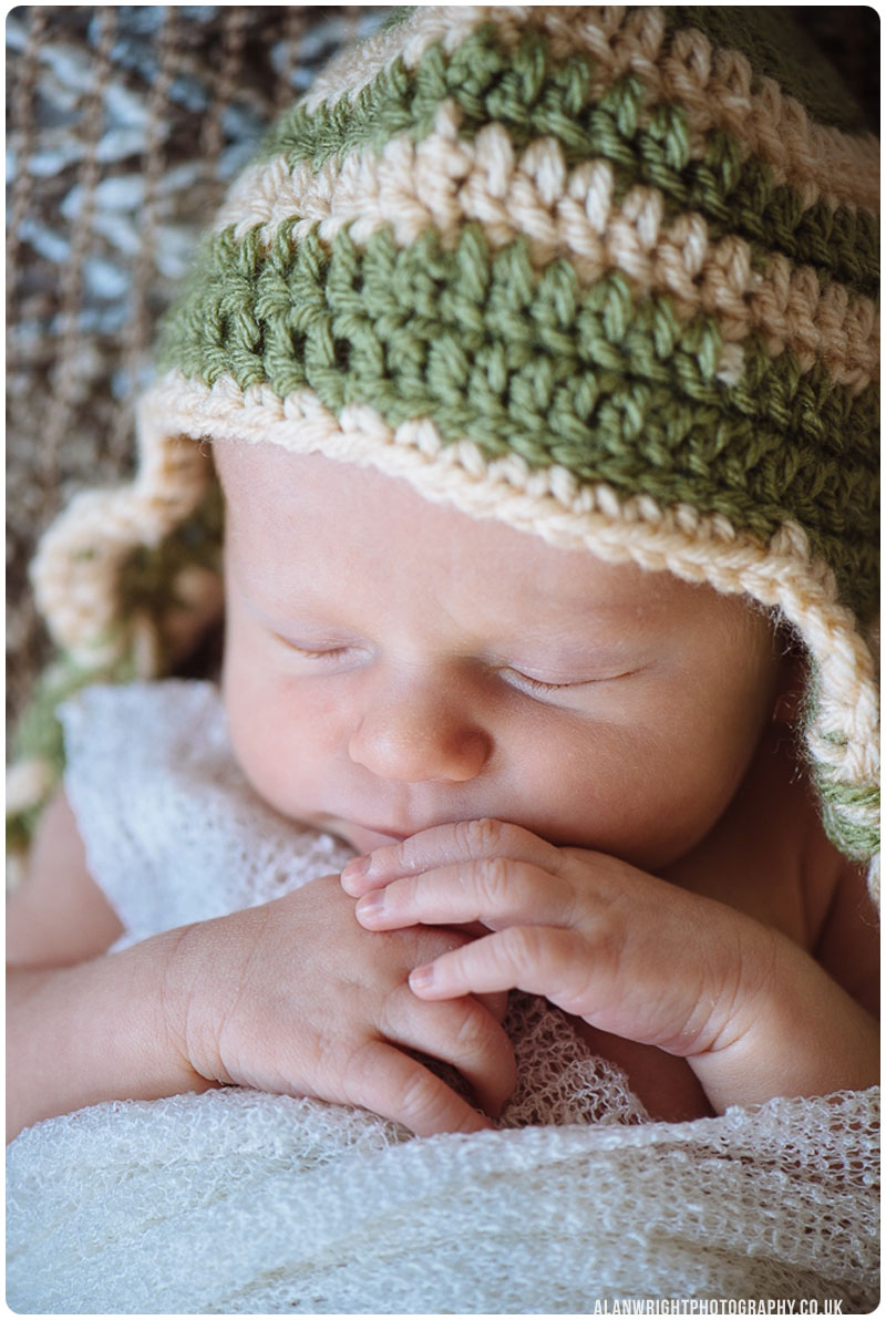 A close up portrait photo of a newborn baby sleeping with hands together
