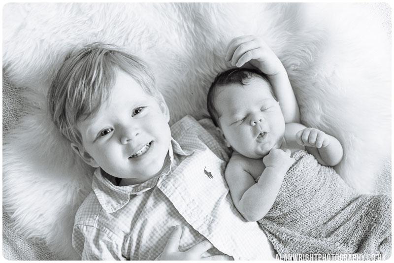 Older brother cuddles his newborn sister