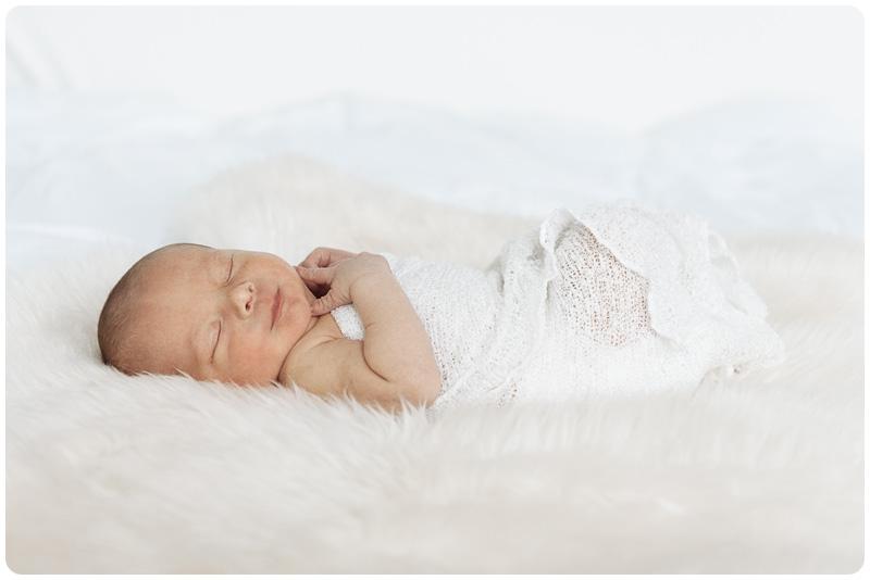 A sleeping newborn baby boy in a wrap