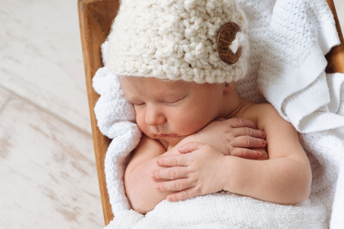 Newborn baby wrapped in blankets sleeps in a basket