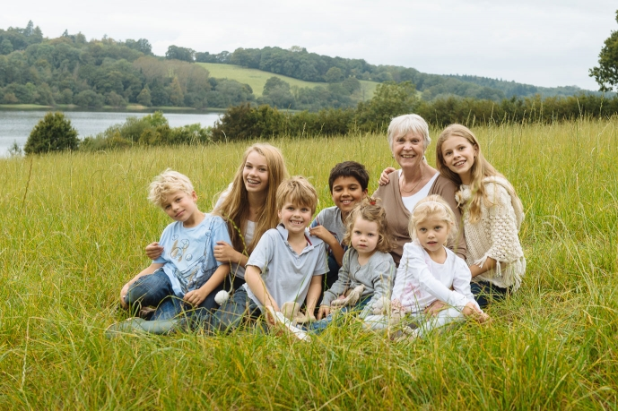 grandmother poses with grand children for family photo