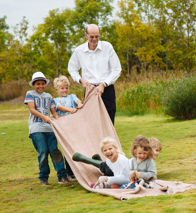 grand dad pulls grand children on blanket