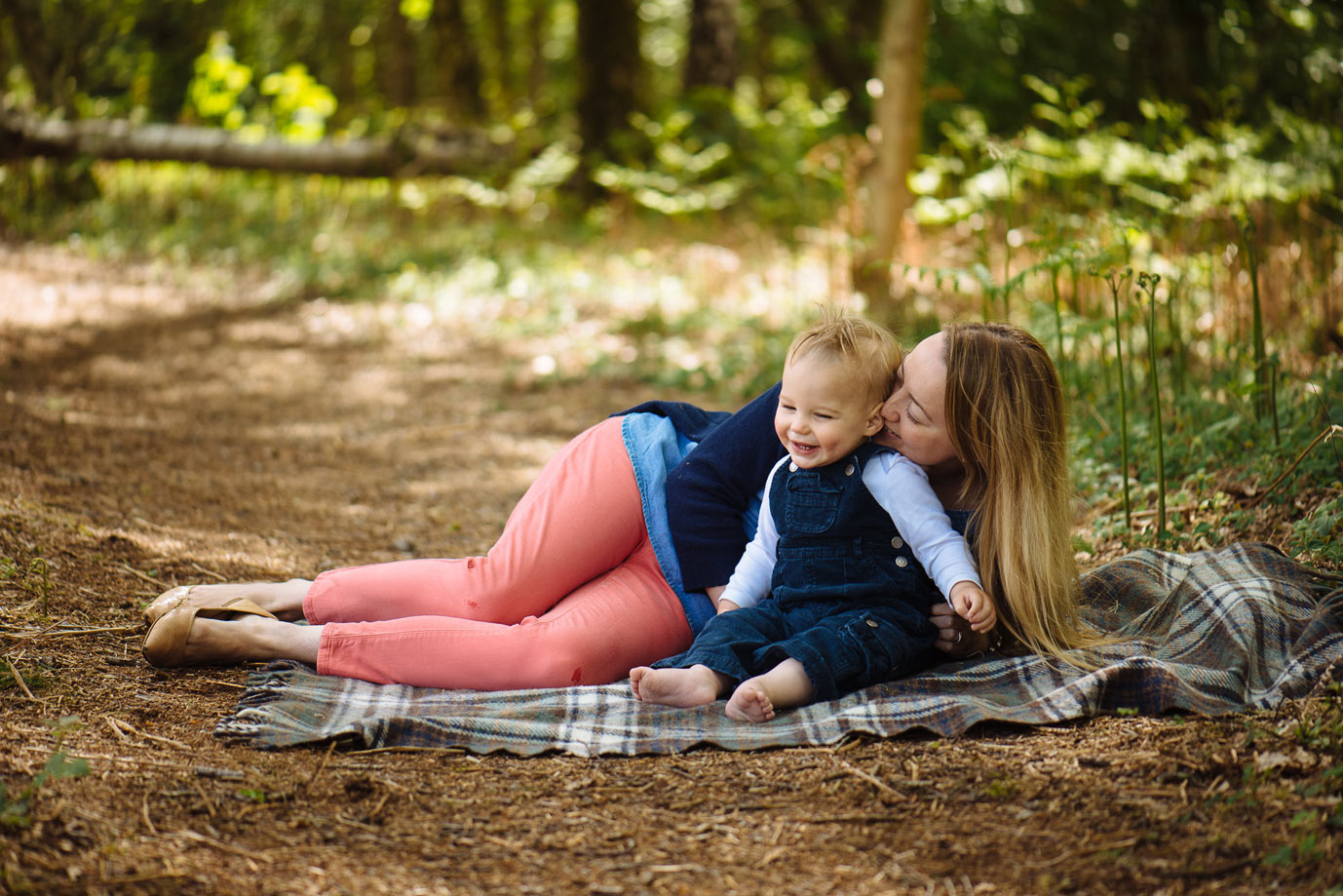 mother and son laying on a blanket in the woods