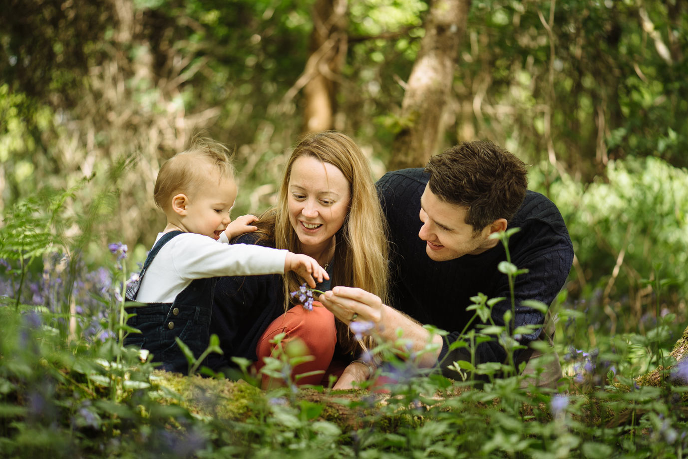 Parents with son in bluebell covered woods