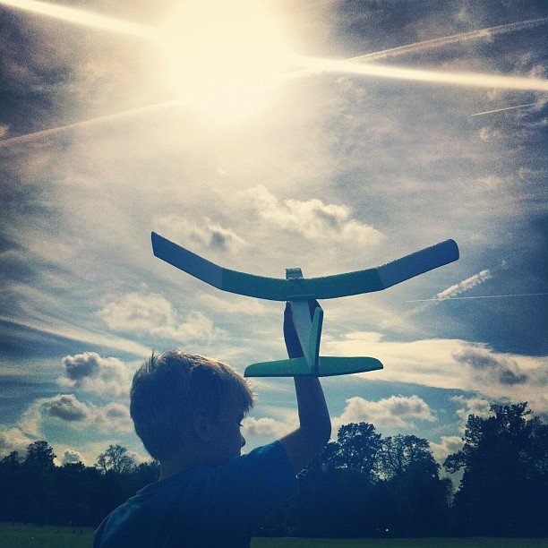 A boy launches a model plane into the sky