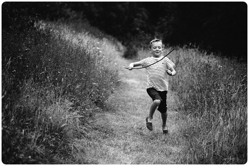 A boy has an adventure in the long grass meadow with a stick as his sword