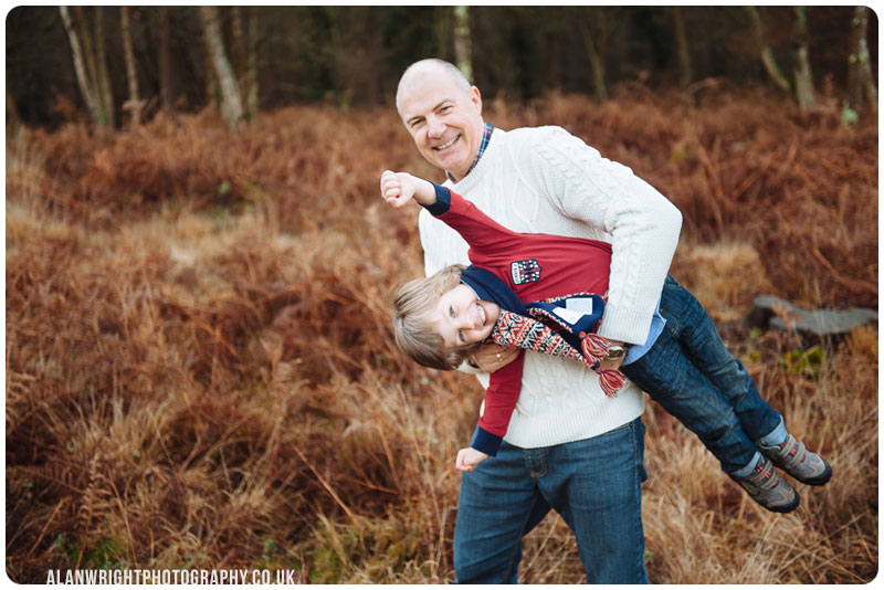 dad carrying off their child who pretends he's superman