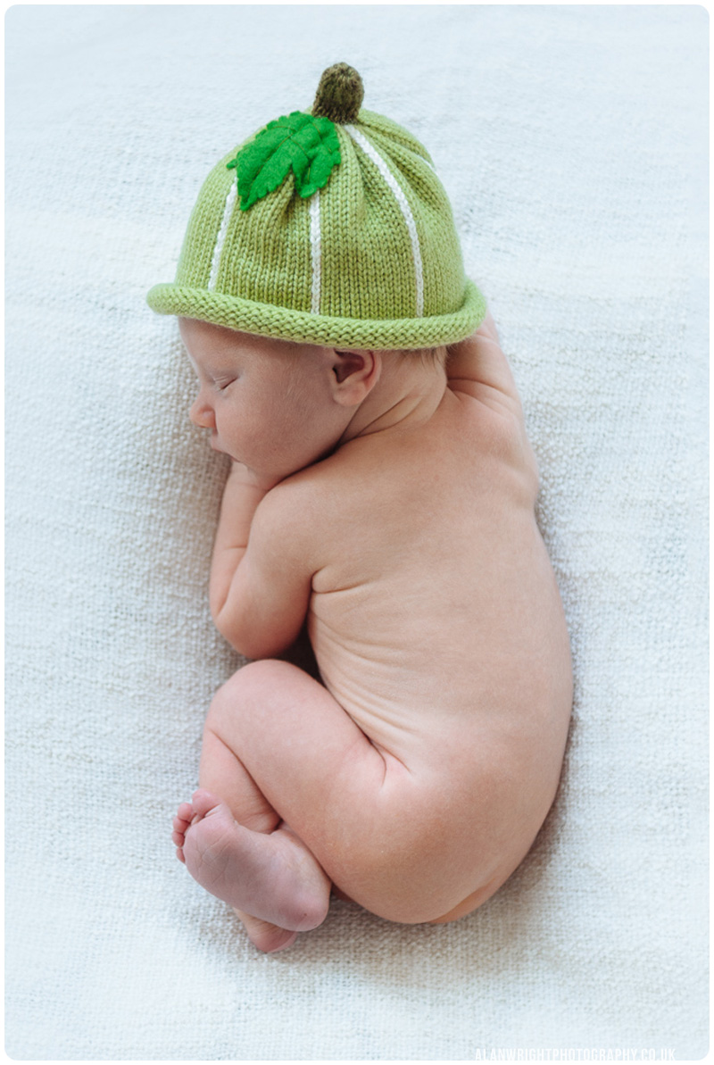Newborn Baby fast asleep wearing a cozy gooseberry hat