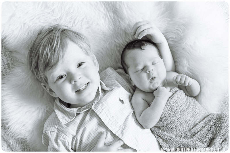 Older brother cuddles his newborn sister