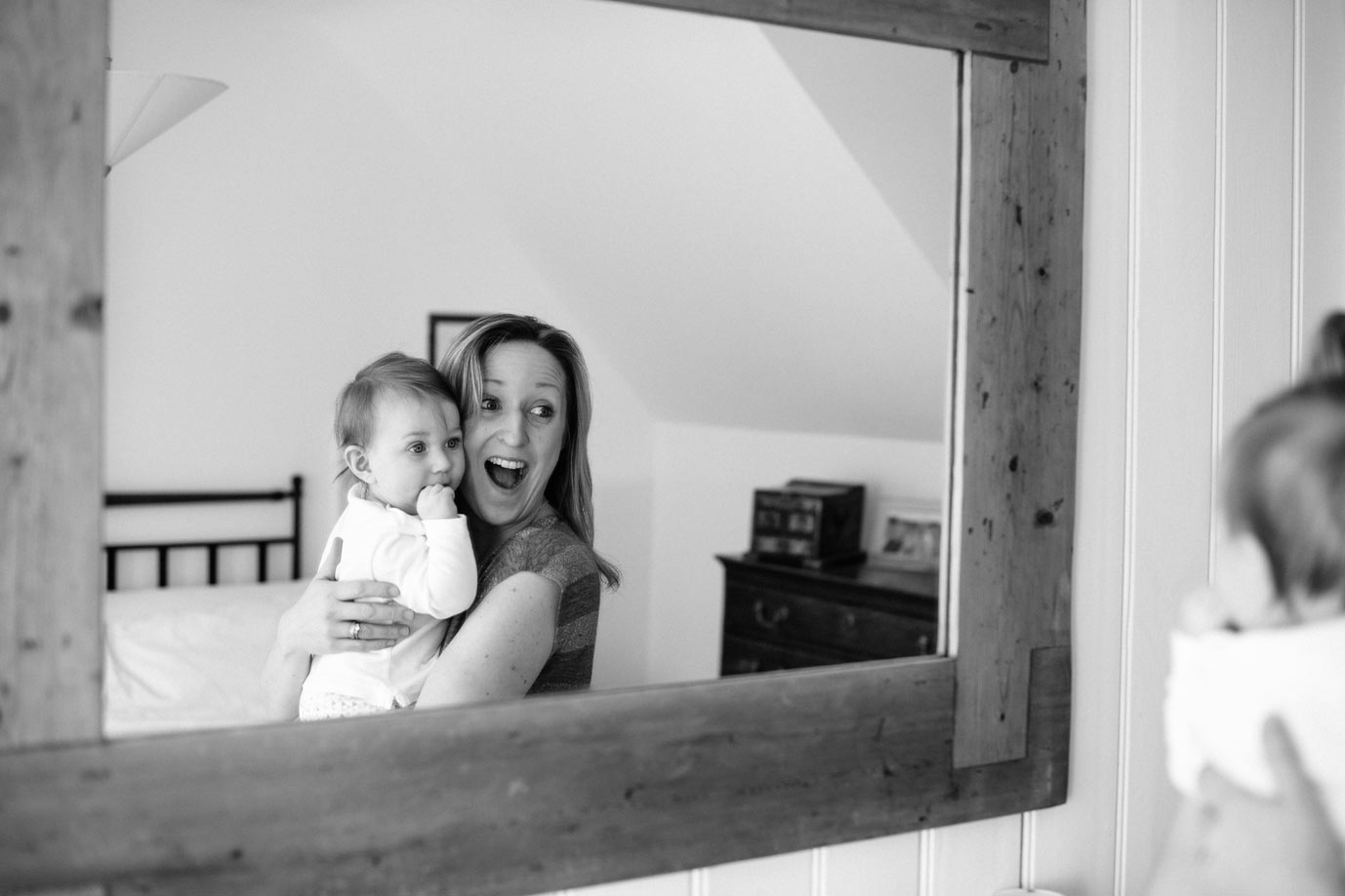 Mother and baby play games with the bedroom mirror